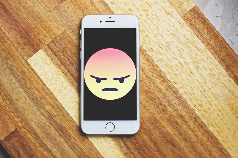 Phone with an angry face emoji filling the screen.