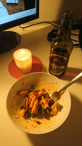 Picture of my spinach and tomato pasta, cider and a lit candle.