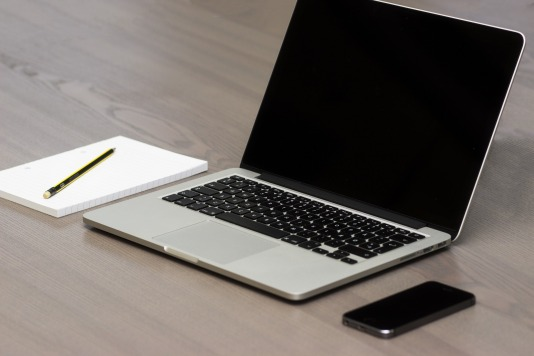 A minimalist desk, a notebook and pencil sits next to a laptop and phone. The rest of the visible desk surface is clear.