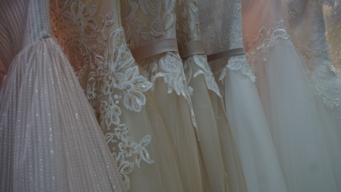 A close-up on dresses in varying but very similar shades of cream and white, with slightly different amounts of floral lace detailing and beading on each.