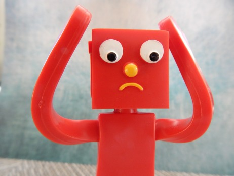 A red plastic block figure has its arms up, hands by its head. Its eyes are wide and concerned, it's frowning in obvious distress.