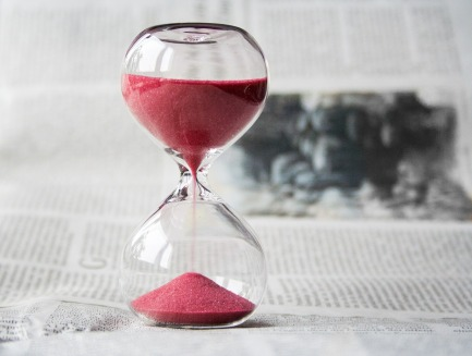 A glass hourglass filled with red sand which is draining through to the bottom half. The hourglass is almost half done.