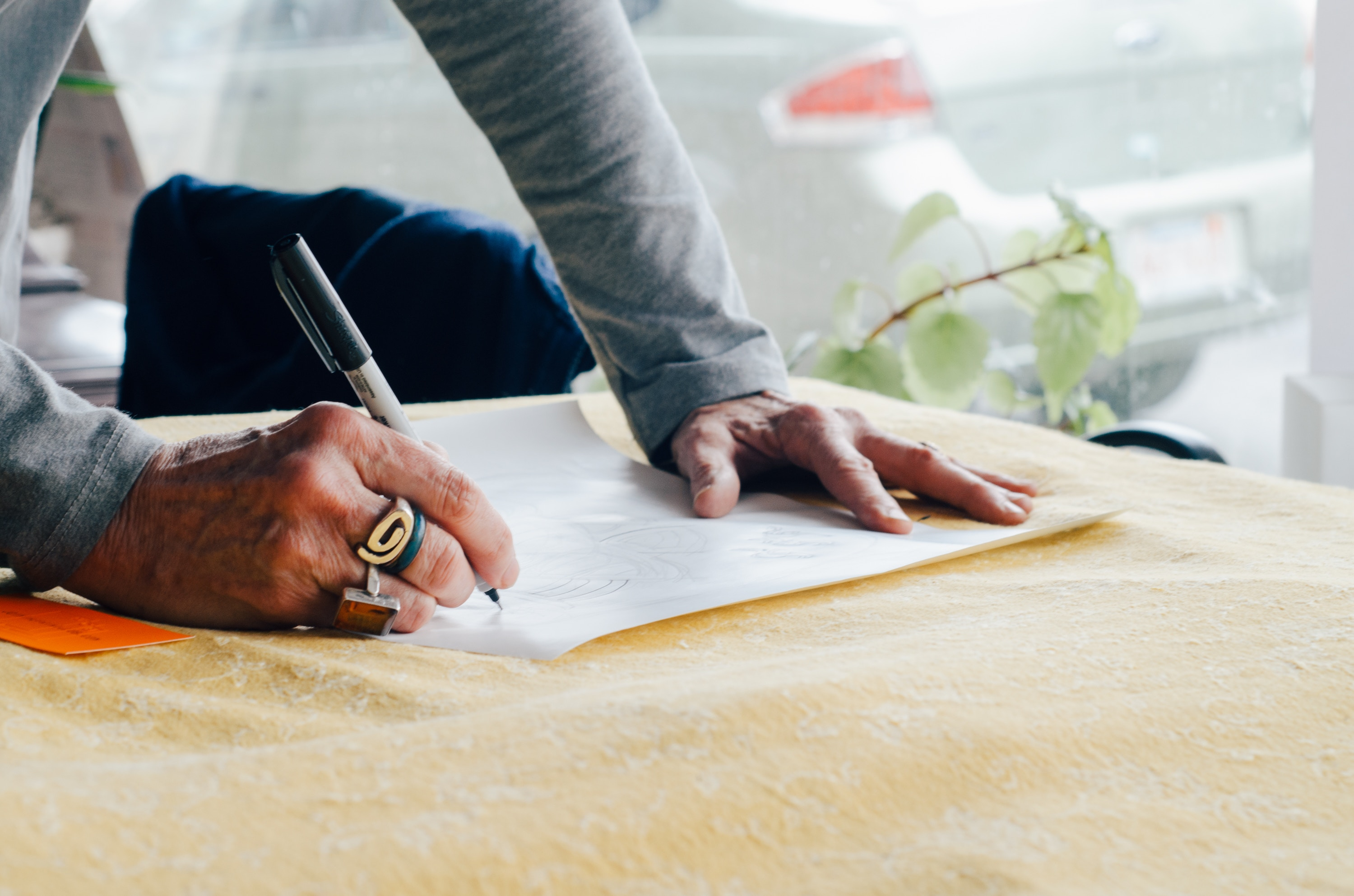 Person writing on plain paper, only the hands and forearms are visible.