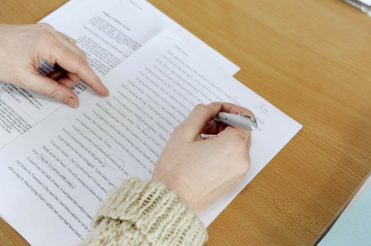 View of a woman's hands as she edits a page of printed writing.