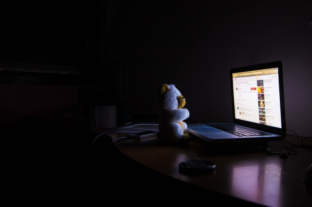 A toy bear sits in front of a laptop in a dark room, illuminated by the glow from the screen.