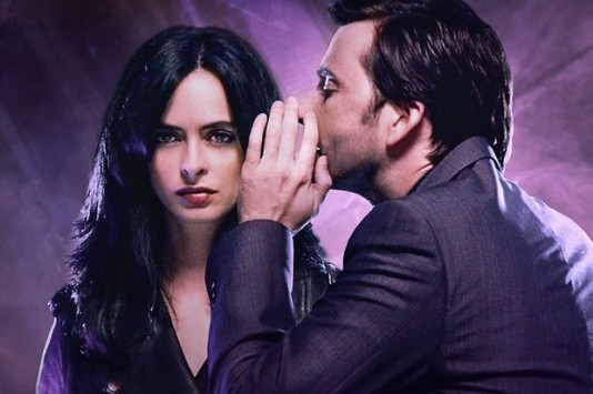 Kilgrave, a man in a suit, whispers menacingly into the ear of Jessica Jones, a young woman with dark hair and a serious expression.