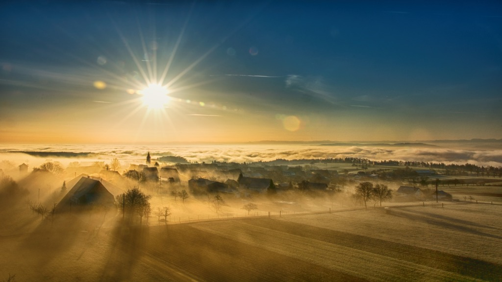 The sun rises over a foggy town.
